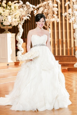 bride in strapless lazaro ball gown with ruffled skirt and beaded belt