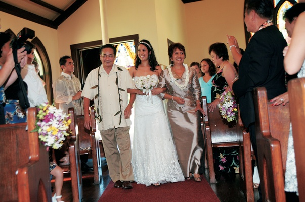 bride and parents walk down aisle at tropical ceremony