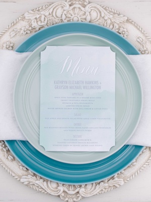 white and blue menu on white napkin blue plate and white detailed charger plate