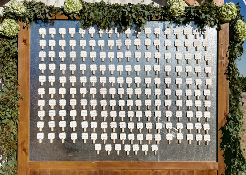 Seating cards with wine corks on chalkboard