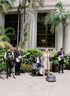 wedding reception cocktail hour woman singer dress men with instruments guitar drums palm trees