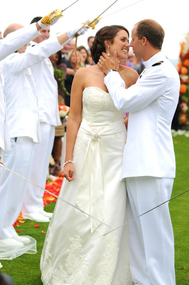 US Navy lieutenant and wife kiss between sword