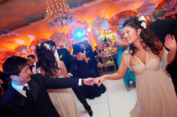 Bridesmaid dancing on white dance floor under chandelier