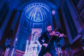 Dr. Draw electric violinist performing at wedding reception old catholic church blue purple lighting