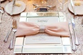 Pink bow napkin tied with crystal ring on mirrored charger