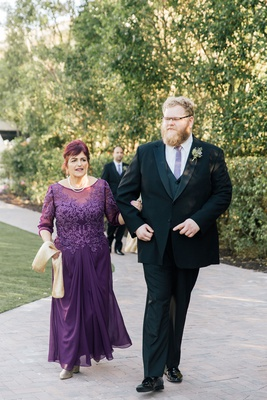 mother of groom in purple gown embroidered bodice three quarter sleeves sash necklace