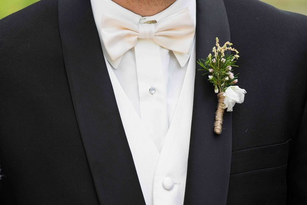 Groom wearing white bow tie and boutonniere in twine