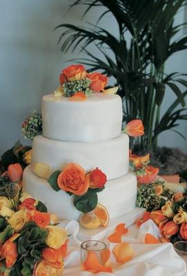 orange roses and lemon and orange wedges adorn white cake