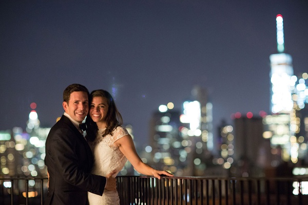 Bride in short sleeve lace wedding dress with groom outside New York City skyline in background