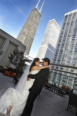 Bride and groom hug on rooftop with pumpkins and skyscrapers