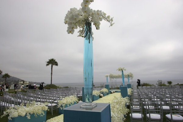 vase filled with blue water and white flowers sits on top of a blue box at end of aisle
