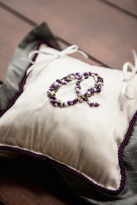 Purple cord on white ring pillow with monogram O in flower appliques