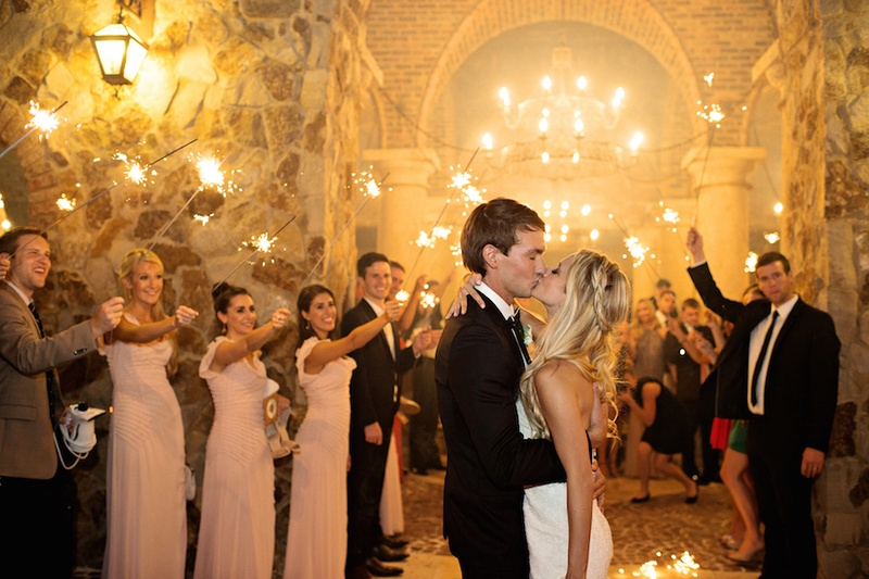 Bride in a strapless Romona Keveza gown kisses groom surrounded by guests holding sparklers