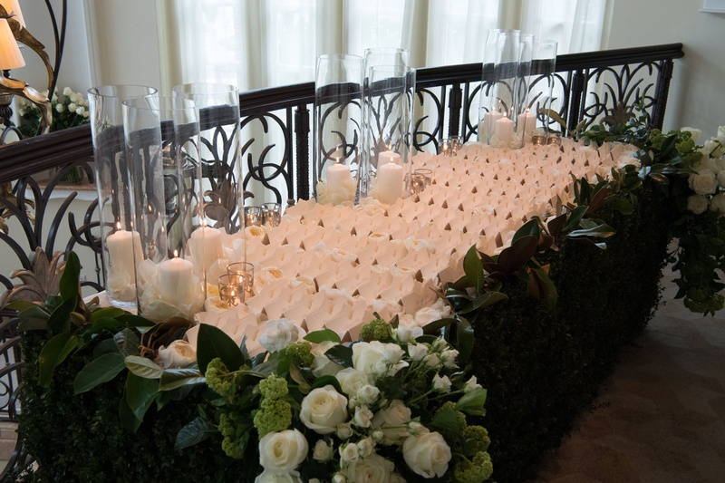 Wedding reception table escort cards white flowers greenery candles in cylinder vases ivory escort