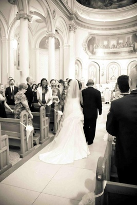 Black and white photo of bride walking down aisle