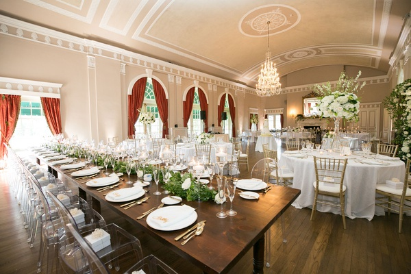 Wedding reception ballroom wood floor red drapes chandelier wood table white linens greenery white