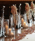 Pillar candles and flowers next to wooden pews