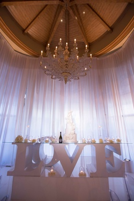 table legs spelling LOVE at reception candles cake wine metallic