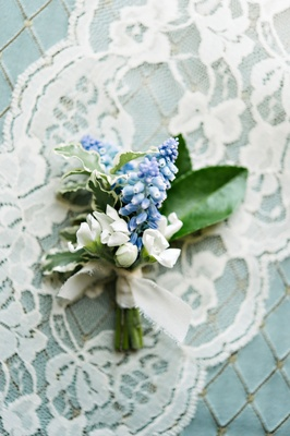 White flower blue flower green leaves boutonniere tied with white ribbon on lace
