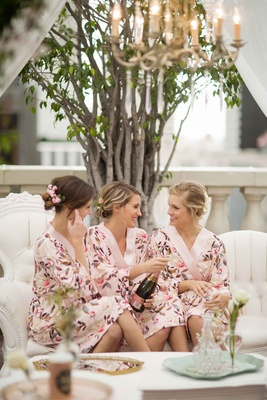 bridesmaids in floral robes popping pink champagne