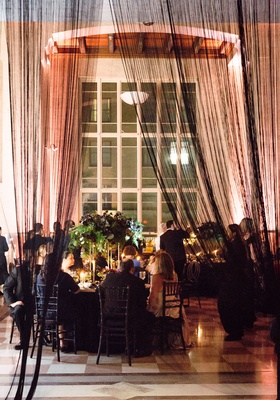 Wedding reception ballroom black sheer drapery at entrance to reception dark flowers greenery candle