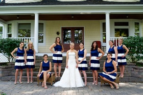 Bridesmaids in blue sleeveless dresses, white stripes on skirts, bride in strapless Vera Wang gown