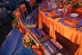 Wedding reception head table with orange tablecloth, napkins, and flowers