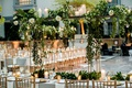 wedding reception long tables gold chairs tall gold riser floating greenery white flowers candles