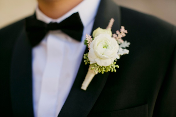 white ranunculus boutonniere with sprigs of pink and green