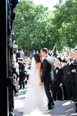 bride in monique lhuillier mermaid wedding dress and groom in gibeon tolbert kiss outside church