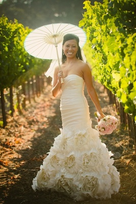 Asian bride in vineyard holding parasol and bouquet