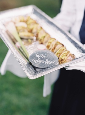 Silver tray with miniature Cuban tacos appetizer hors d'oeuvre with river rock calligraphy sign
