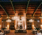 Wedding reception tall drapery crystal chandeliers with wood walls and rustic elements