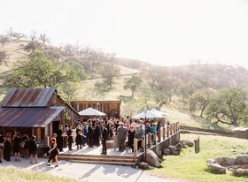 Wedding guests mingling on wooden deck