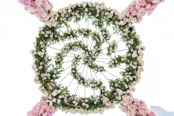 Top of flower ceremony structure spiral greenery white rose pink rose flowers