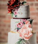 three tier wedding cake with light gray fondant, hand painted pink flowers, gold leaf, sugar dahlias