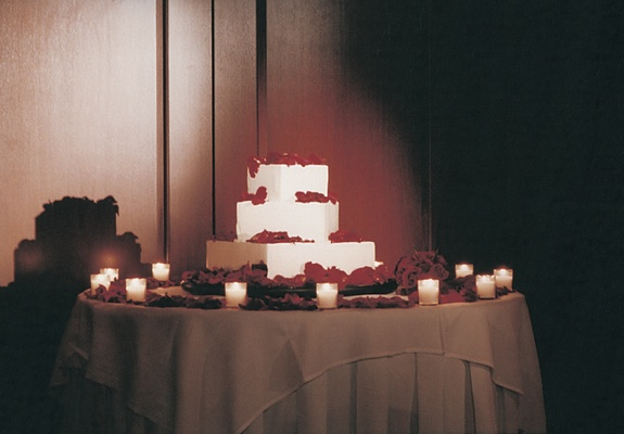 Wedding cake surrounded by roses and candles