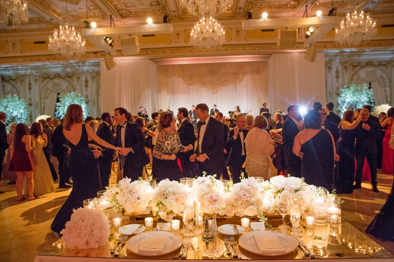 Wedding reception guests on dance floor view from bride and groom seats in ballroom chandeliers