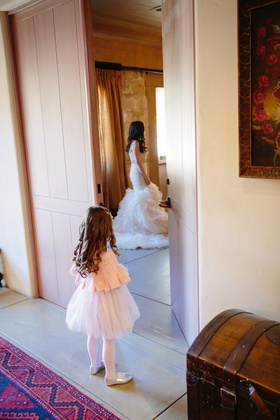 flower girl in pink cardigan, tulle skirt, looks at bride