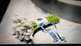 Bride's bouquet of white flowers is tied with a light blue ribbon