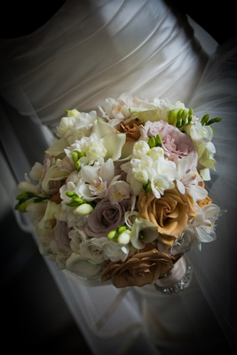 Bride carrying roses, calla lilies, and orchids