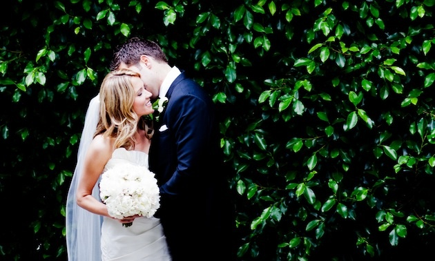Bride and groom in front of hedge at wedding