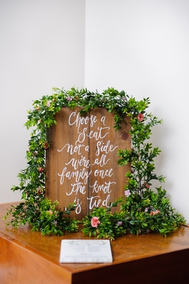 White calligraphy on wood sign with green garlands