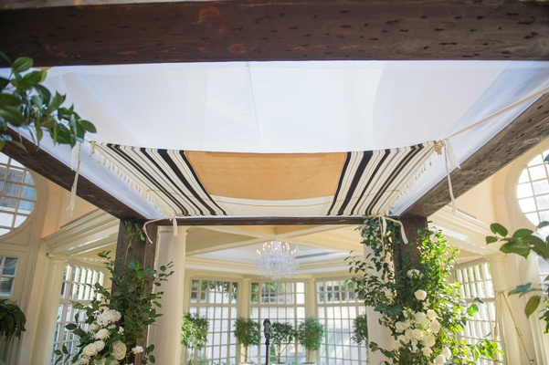 a striped tallit stretched across the top of a couples chuppah for their traditional Jewish ceremony