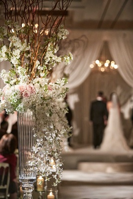 Wedding ceremony aisle flower arrangement with glass vase and branches, white pink flowers