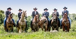 Groom and groomsmen in cowboy hats and jeans on horses