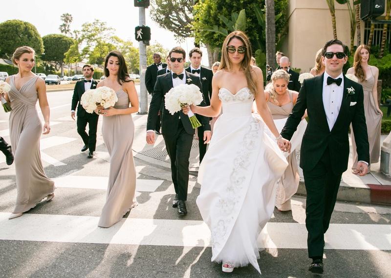 Bride in Oscar de la Renta wedding dress groom in tuxedo bridesmaids groomsmen walking in street