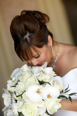 Bride smelling ivory flowers on wedding day