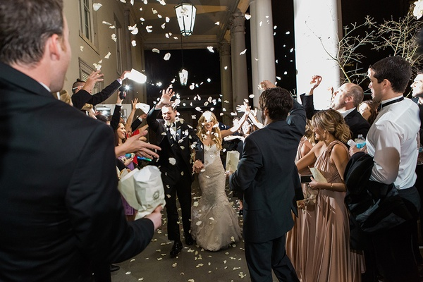 Throwing flower petals at the newlyweds during their wedding getaway grand exit