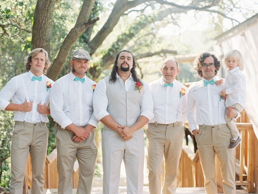 Groomsmen in white dress shirts, turquoise bow ties, tan vest and slacks khaki pants